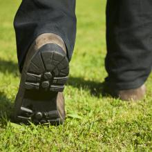 Southern Spary lawn care technician walking on green grass that has been cured of brown patch